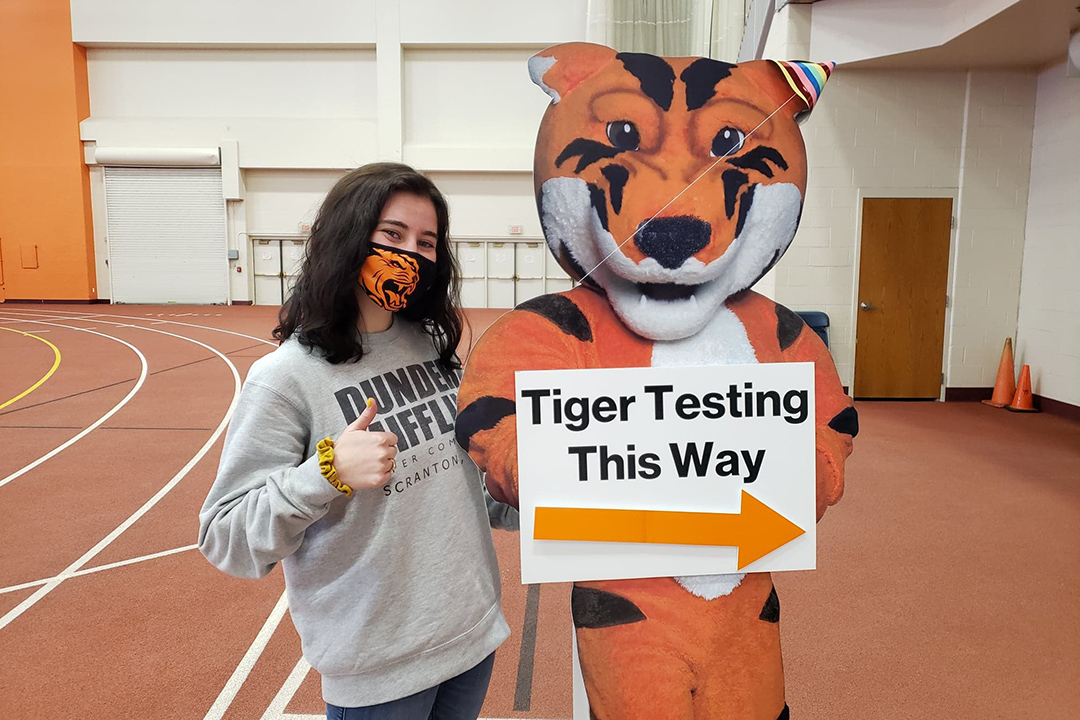 student poses with cardboard cut-out of tiger mascot with sign Tiger Testing This Way.