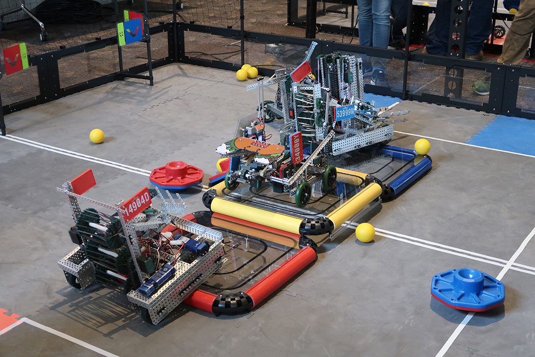 Three hand-crafted robots moving around an enclosed area.