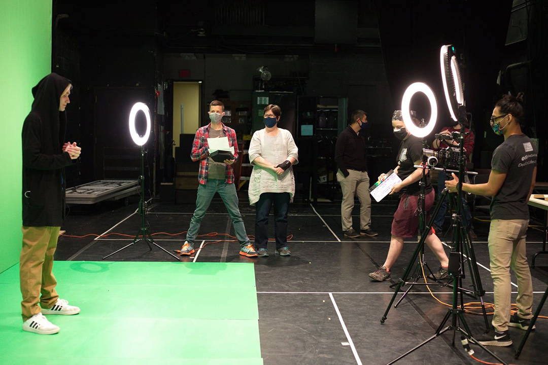 several students filming a student in front of a green screen.