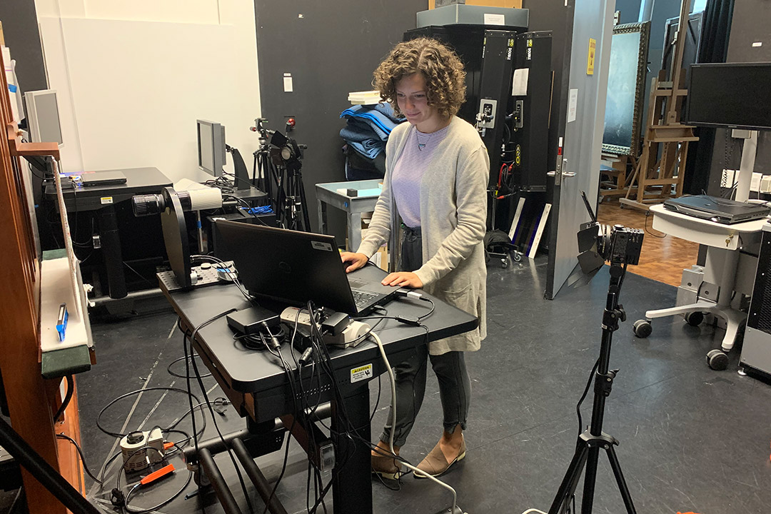 student working on laptop at a standing desk.