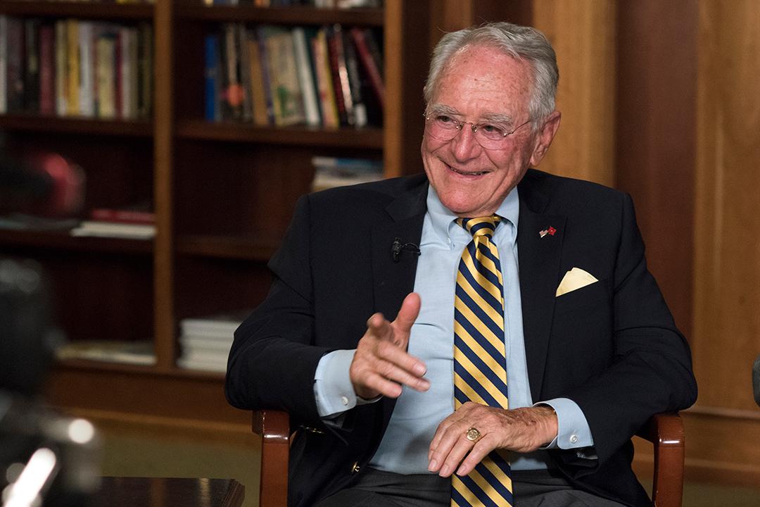 RIT President Emeritus M. Richard Rose sitting in a chair.