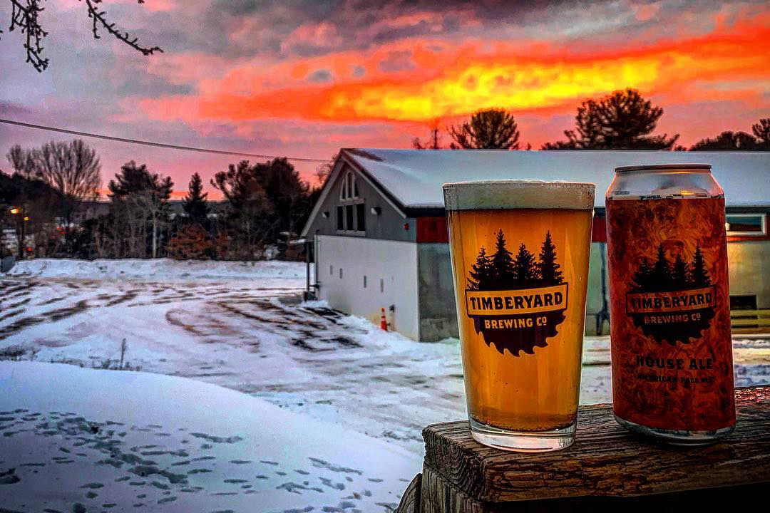 can and glass of beer in foreground of snowy scene with brewery in background.