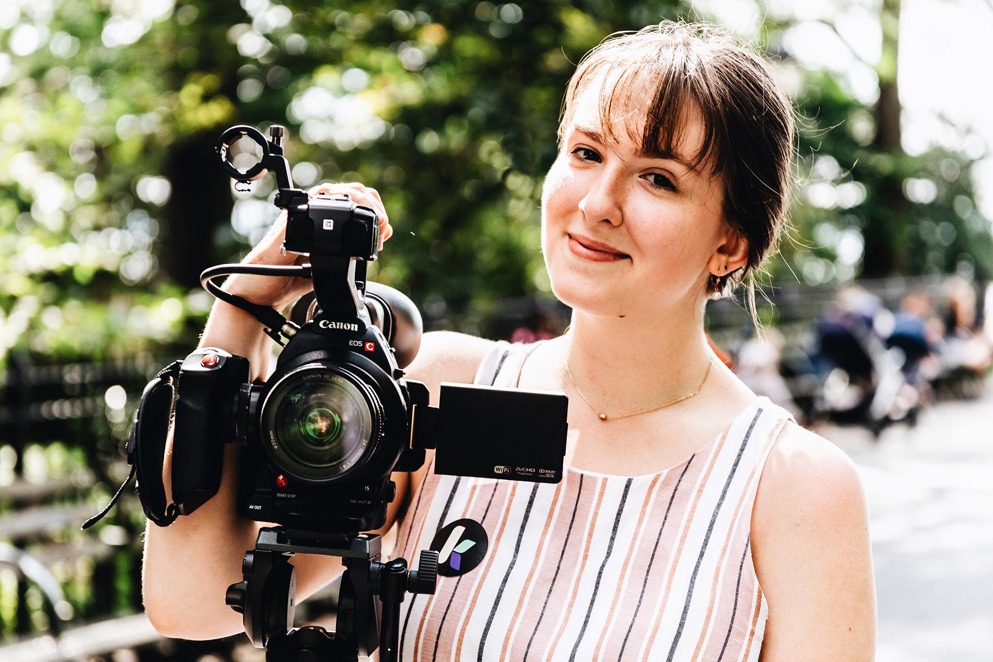 Trisha Pickelhaube stands behind a camera on a tripod.