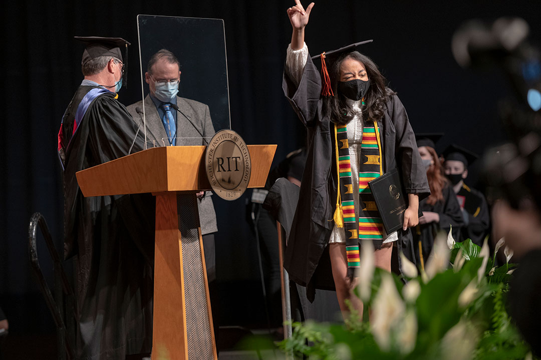 Graduate pointing into the air in celebration while crossing stage.