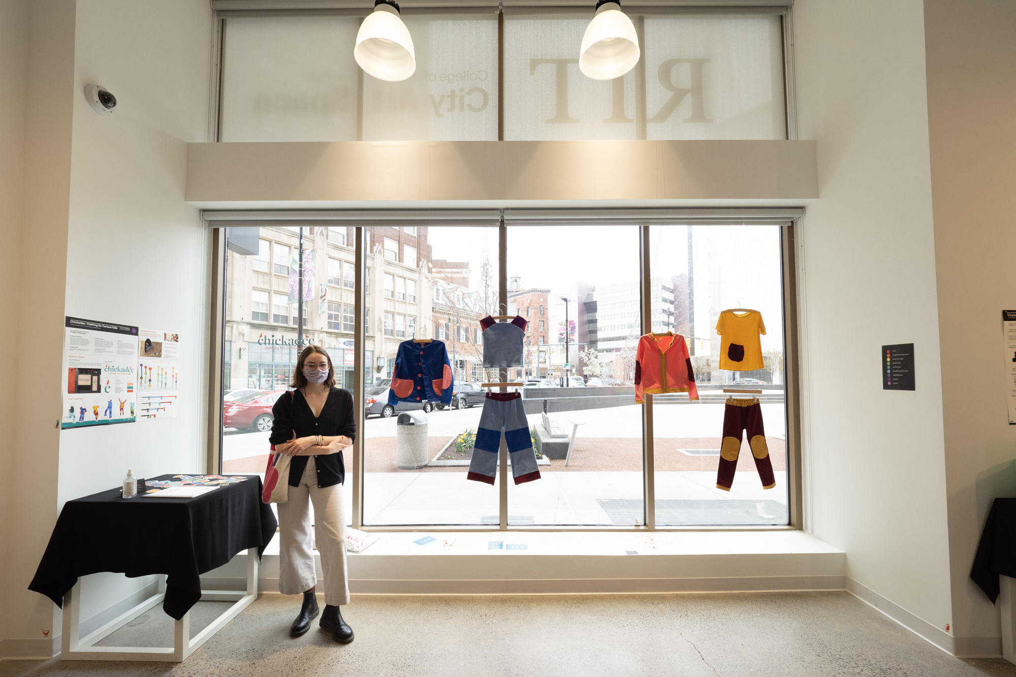 Daeya Shealy stands beside a display of the sustainable clothing line she designed in RIT City Art Space.