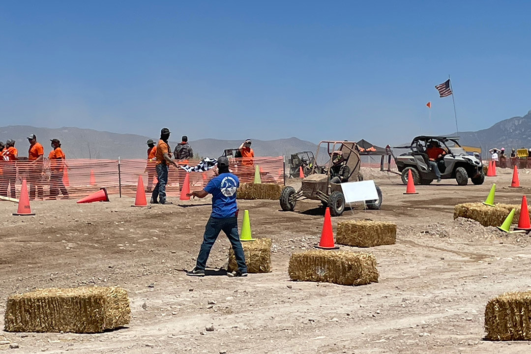 baja cars driving through maze of cones and hay stacks.