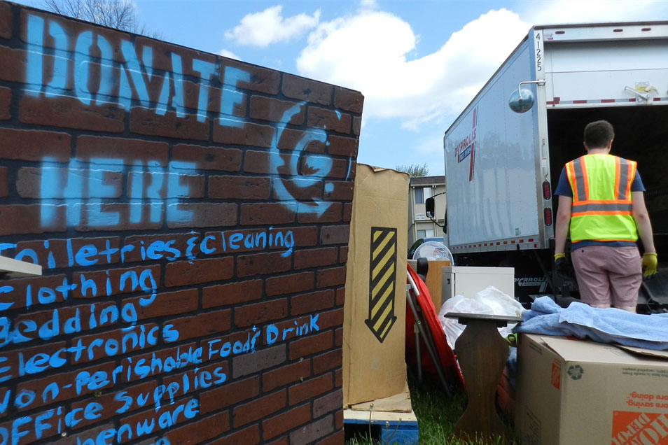 """worker loading used items into a box truck next to sign that reads """"Donate Here."""""""