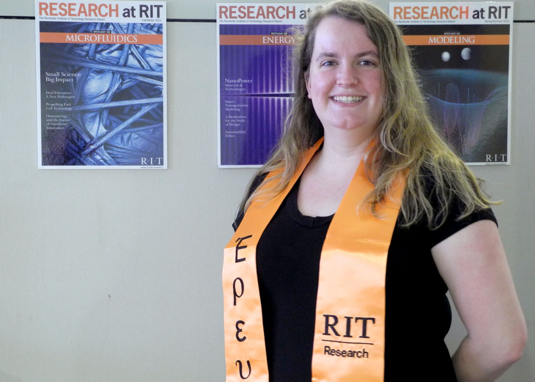 """A woman wearing an orange sash with the words """"RIT Research"""" embroidered on it in black."""