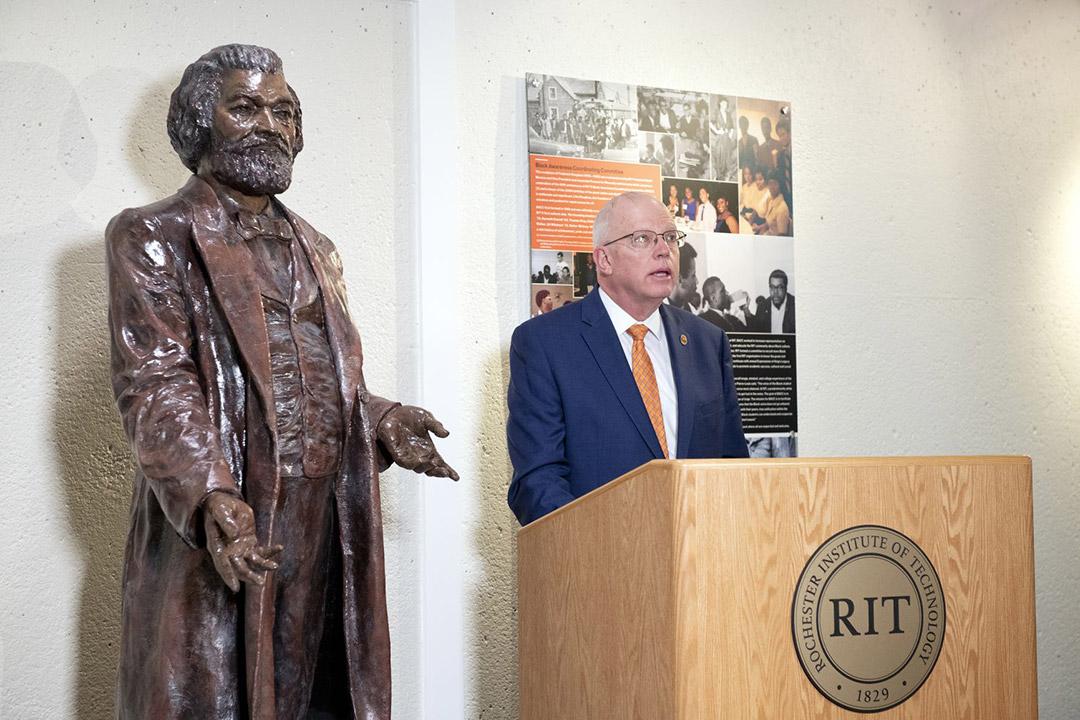 RIT President David Munson standing at a podium next to a statue of Frederick Douglass.