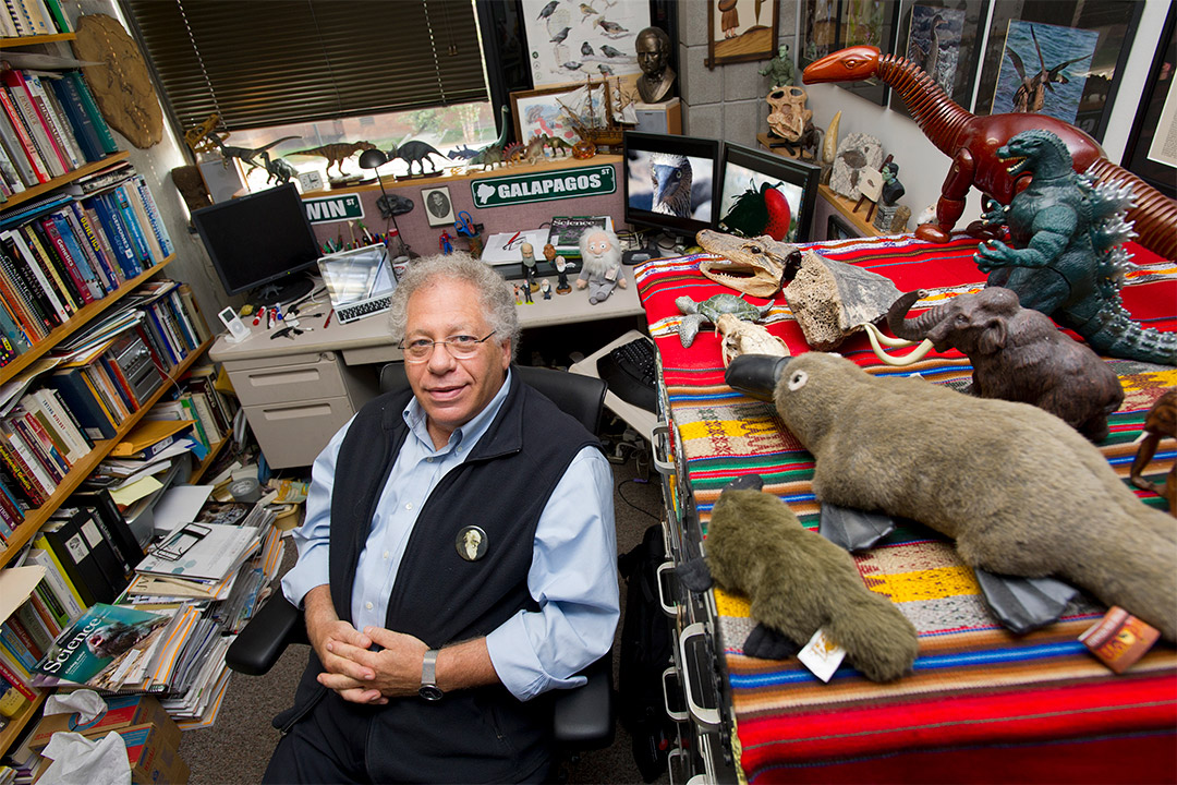 professor sitting in his office surrounded by information about the Galapagos.