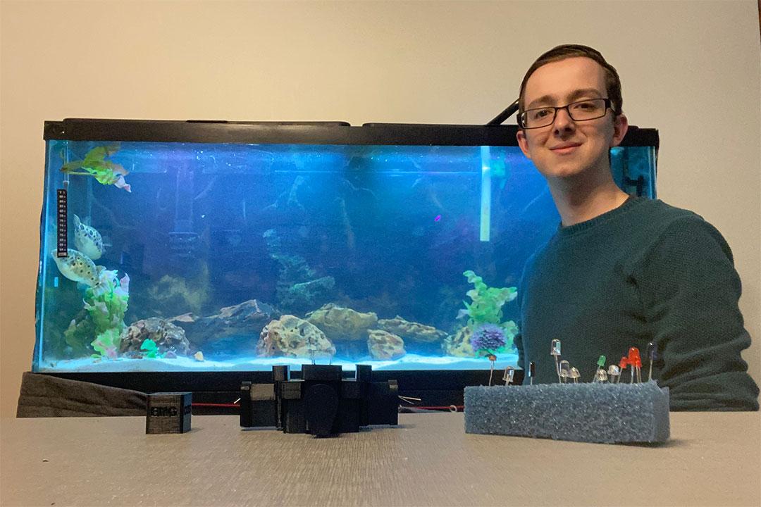student posing with aquarium tank and homemade measuring equipment.