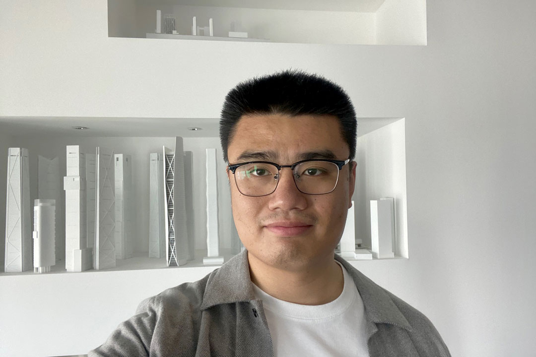 A man wearing glasses poses for a photograph with architectural models.