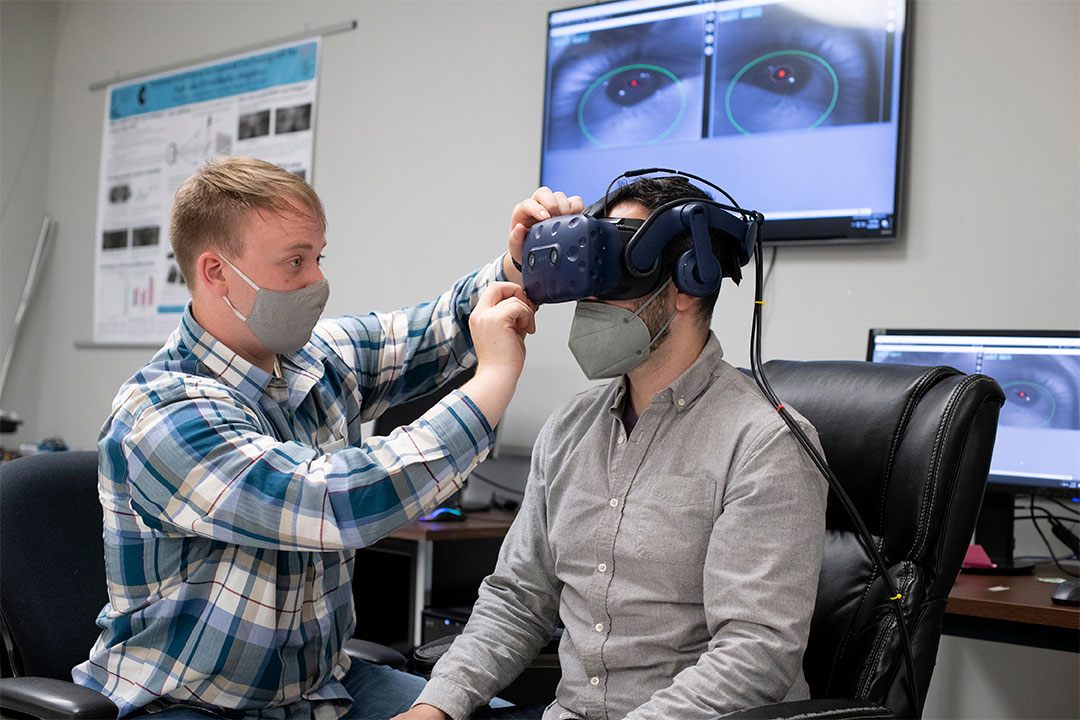 A student adjusts a virtual reality headset on another student.