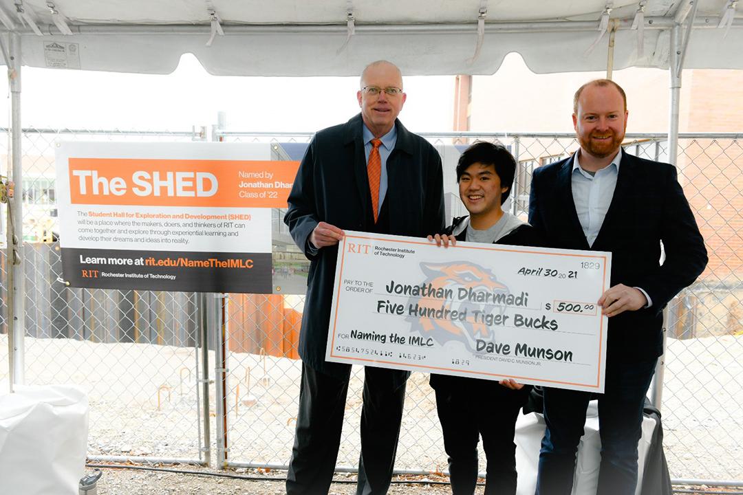 Three men standing with a giant check for 500 dollars. The sign behind them says The SHED.