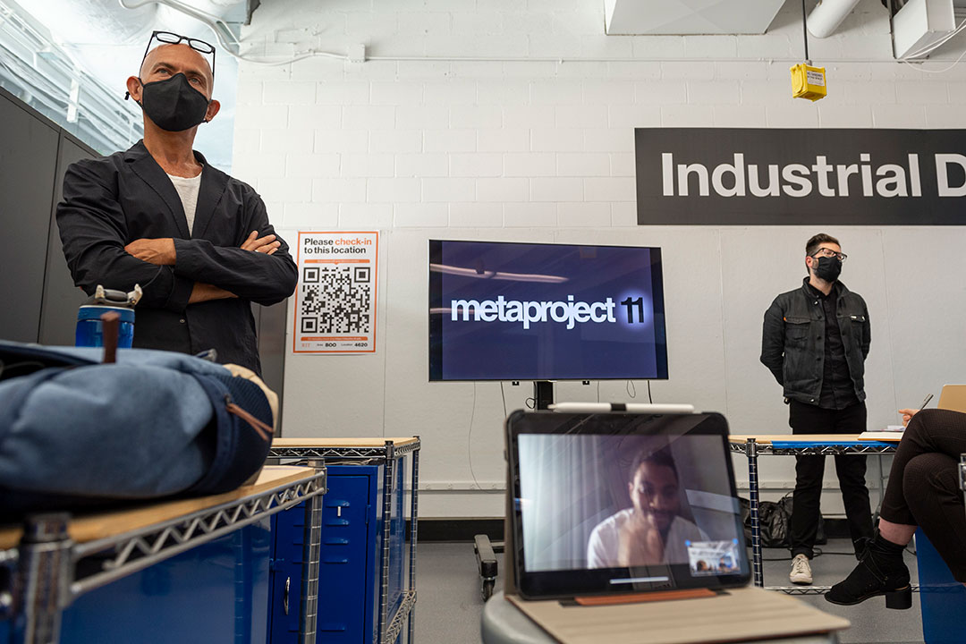 two presenters standing on either side of a TV screen that says: metaproject 11.