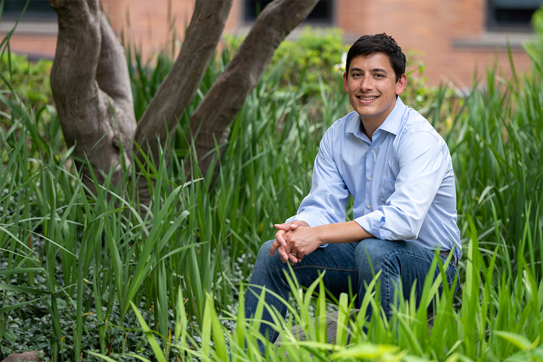 environmental portrait of Tony Wong sitting outdoors near a tree and tall grass.
