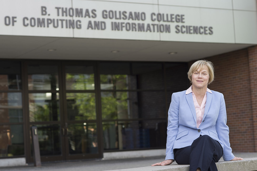 GCCIS dean sitting outside of the computing college building.