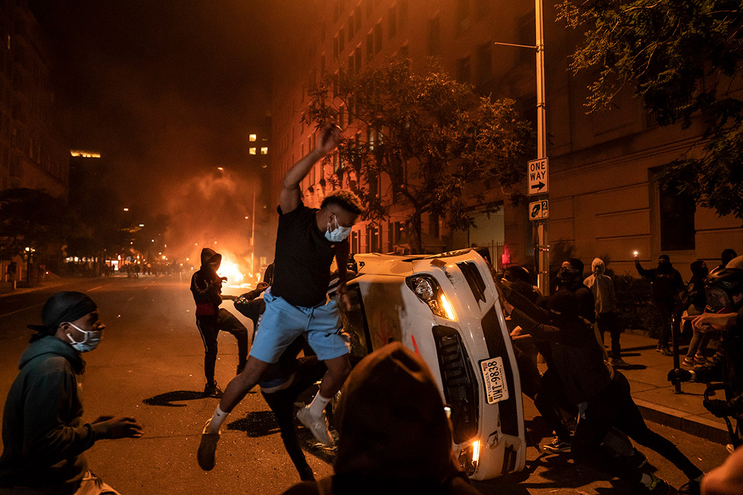 protestors overturning a car in a street at night.
