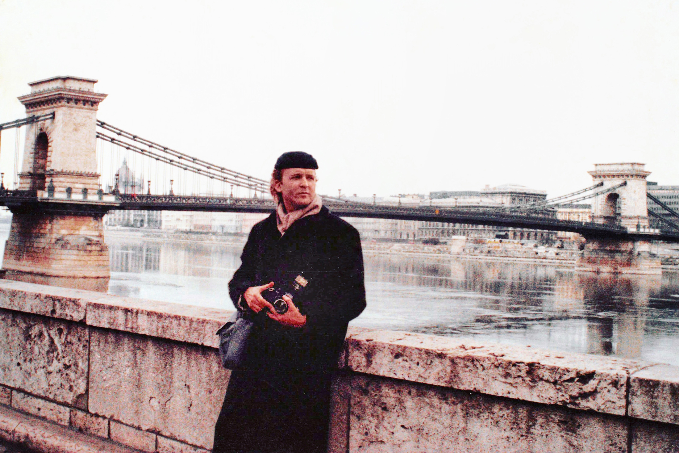 A 1990 photo of Frank Deese holding a camera with water and a bridge in the background.