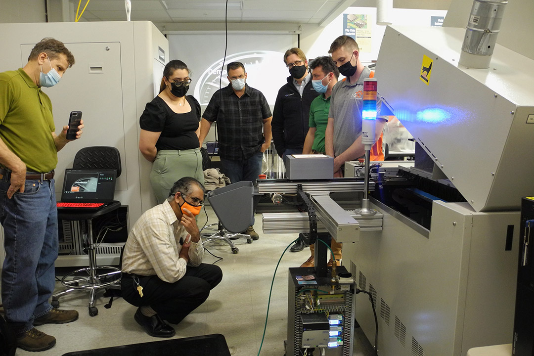 students and faculty looking at an industrial convection reflow oven.