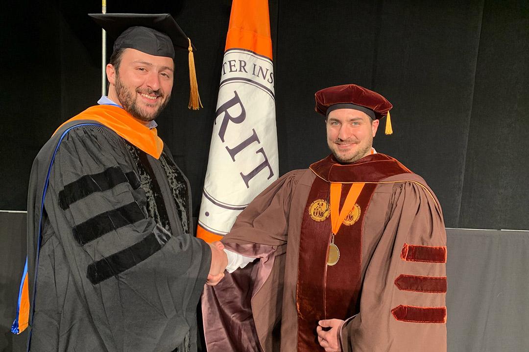 student and professor dressed in graduation regalia shaking hands.