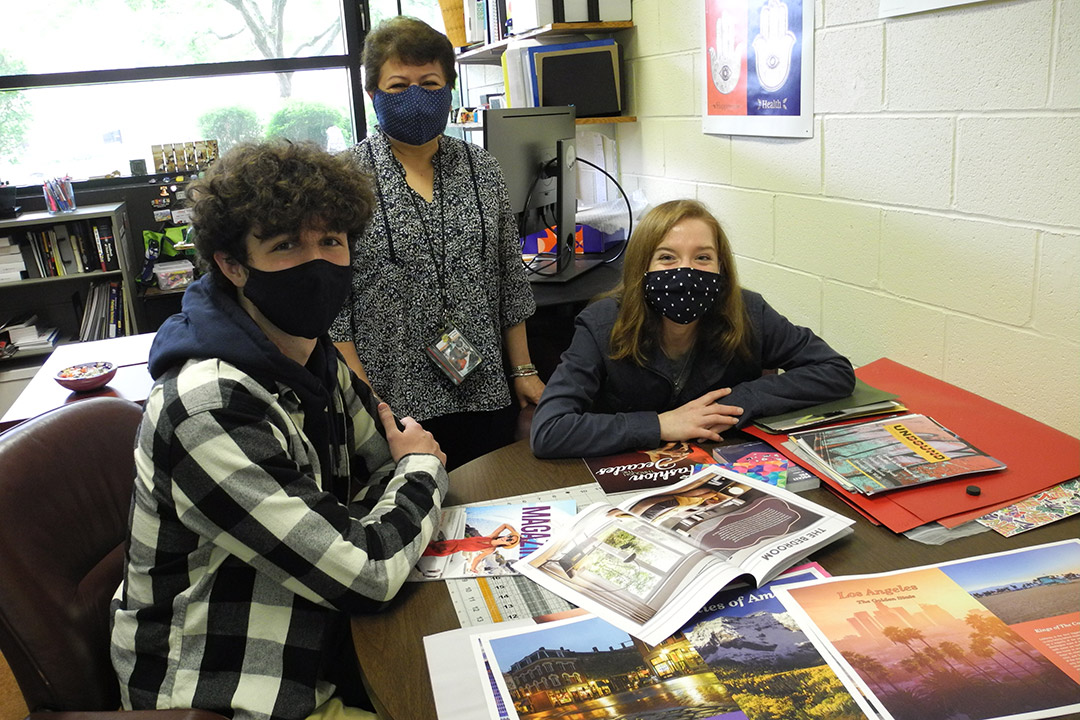 two students and a professor posing with magazine spreads on a table.