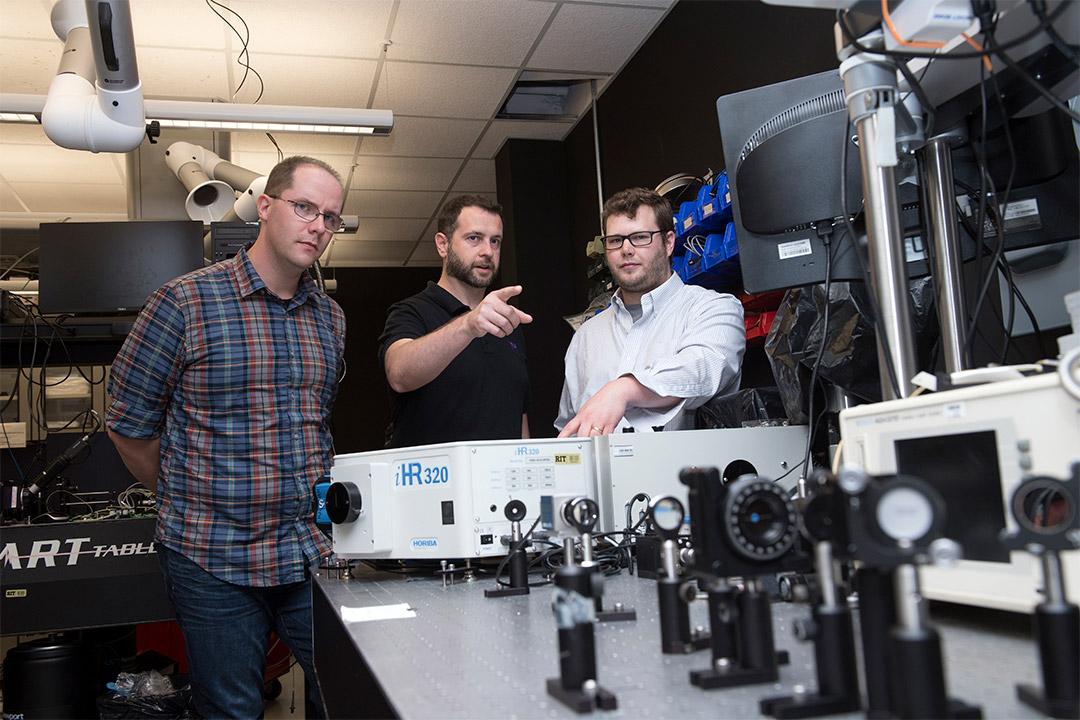 three researchers working with optics and photonics equipment.