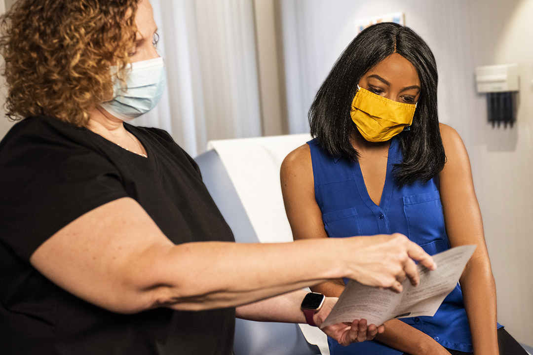 two women wearing face masks looing at a pamphlet in a doctor's office.