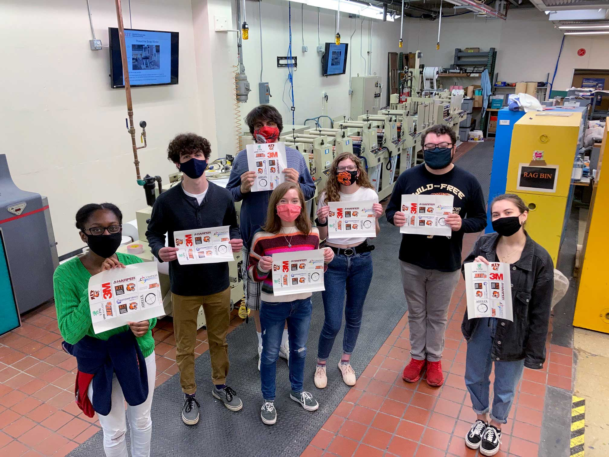 """Students holding flexographic labels printed during """"Recognition Run"""""""