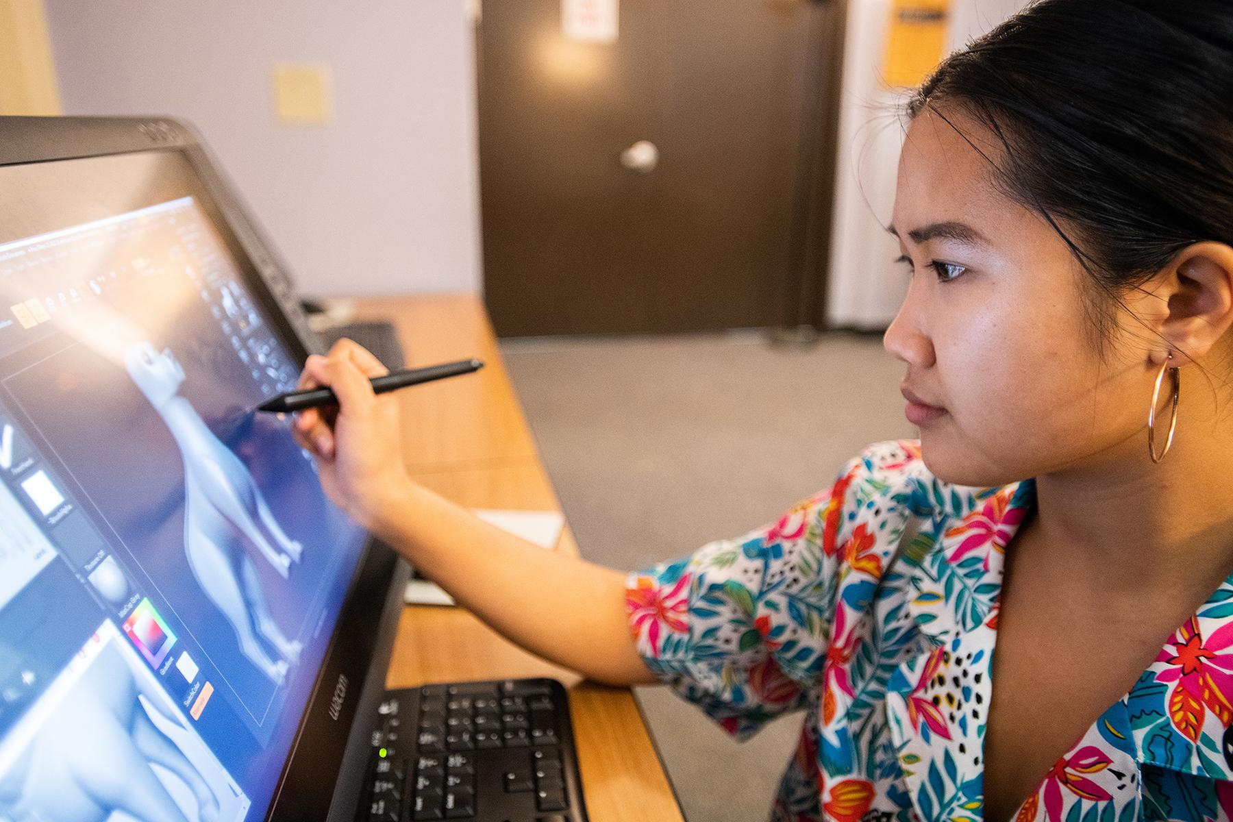 Stephanie Chan digitally illustrates in a computer lab.