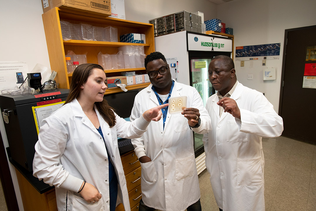 two professors and student wearing lab coats looking at bacteria sample.