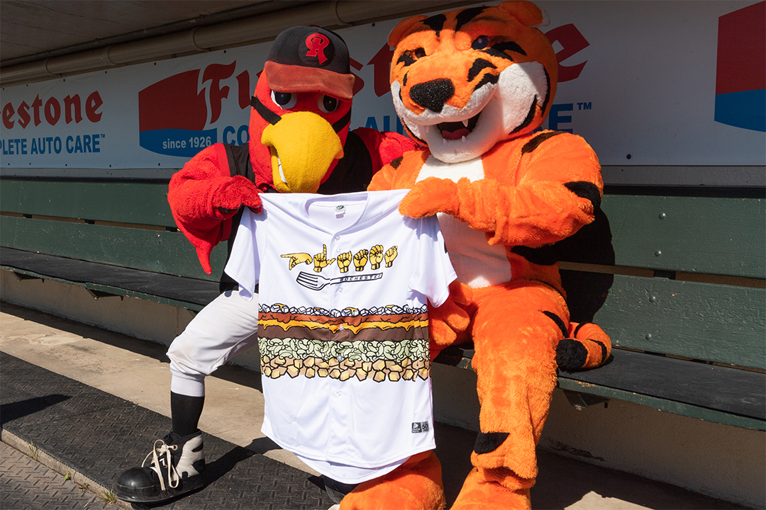 """A mascot bird and a mascot tiger hold up a baseball jersey that says """"Plates"""" fingerspelled in ASL"""