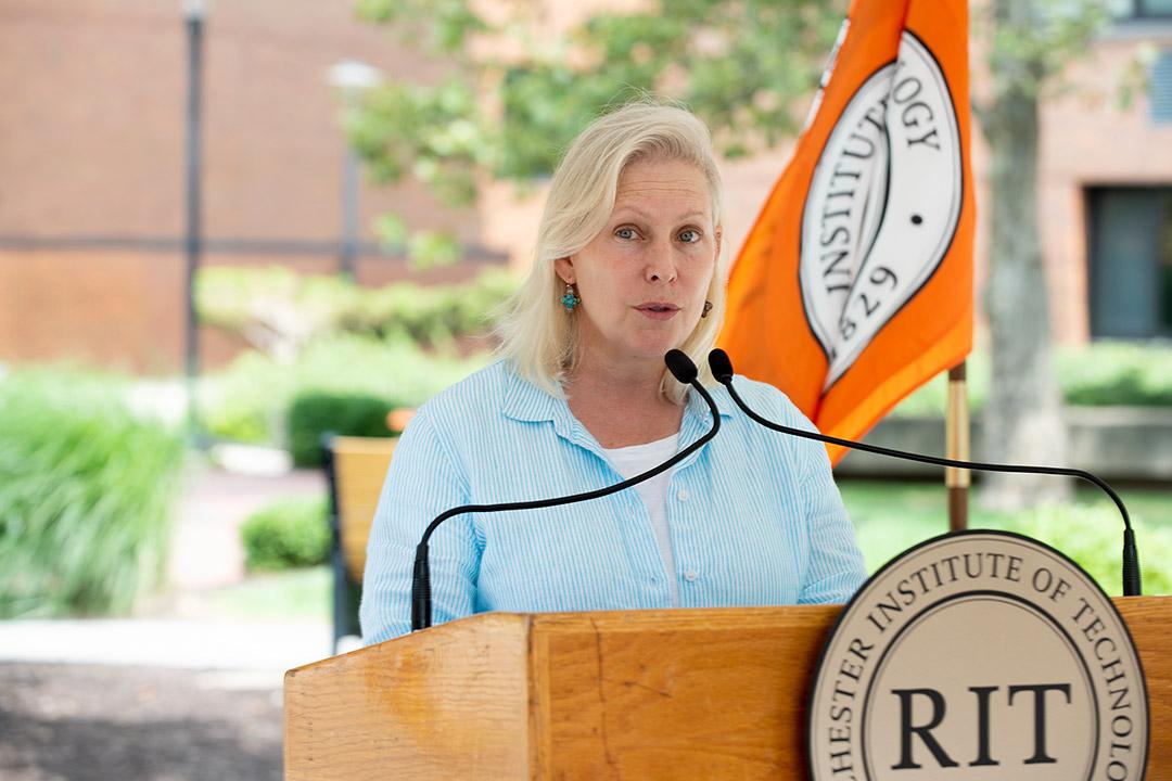 Senator Kirsten Gillibrand speaking at a podium outdoors.