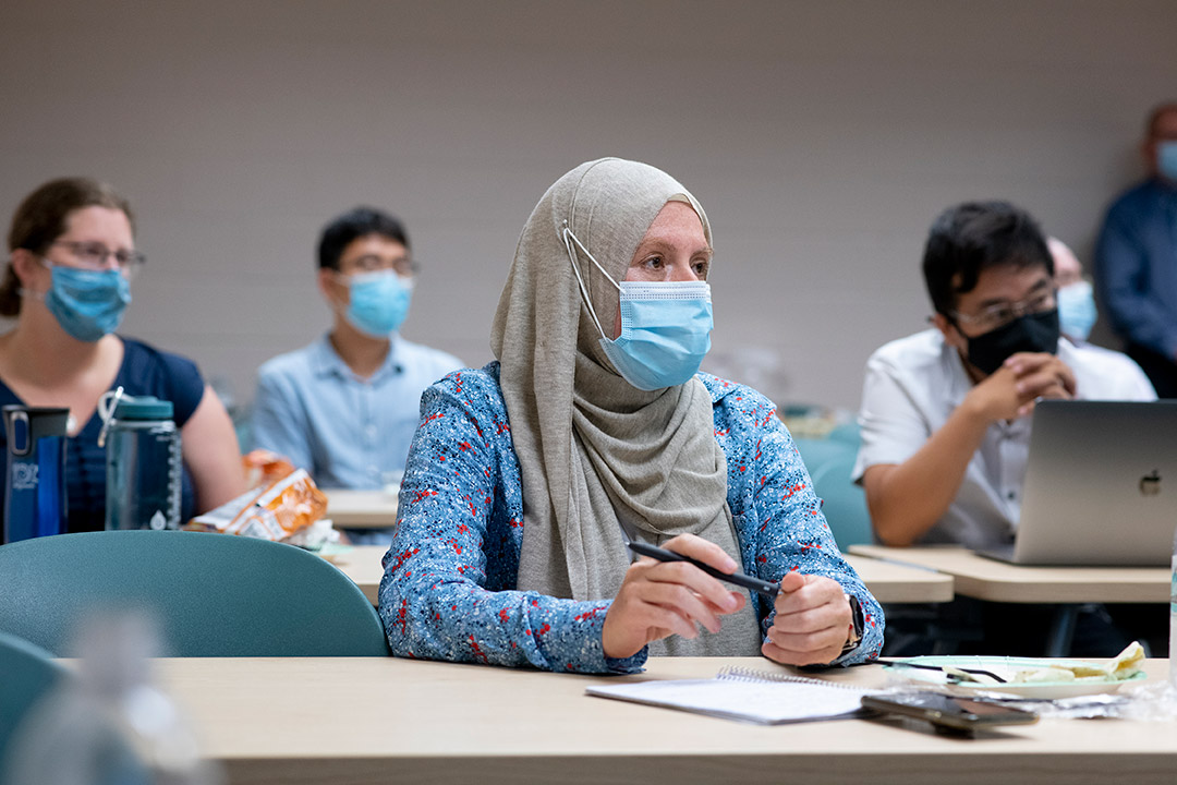 people wearing face masks seated at long tables attending a workshop.
