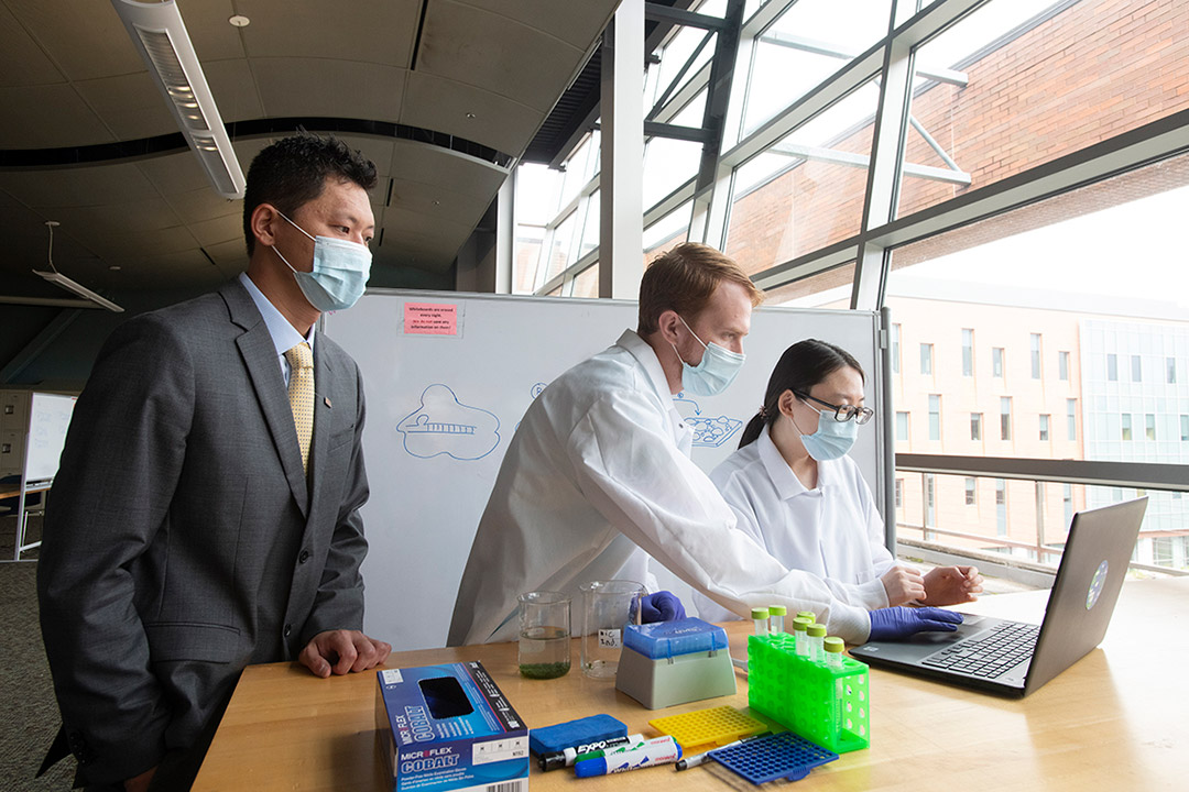 researchers looking at a laptop on a table with beakers and vials.