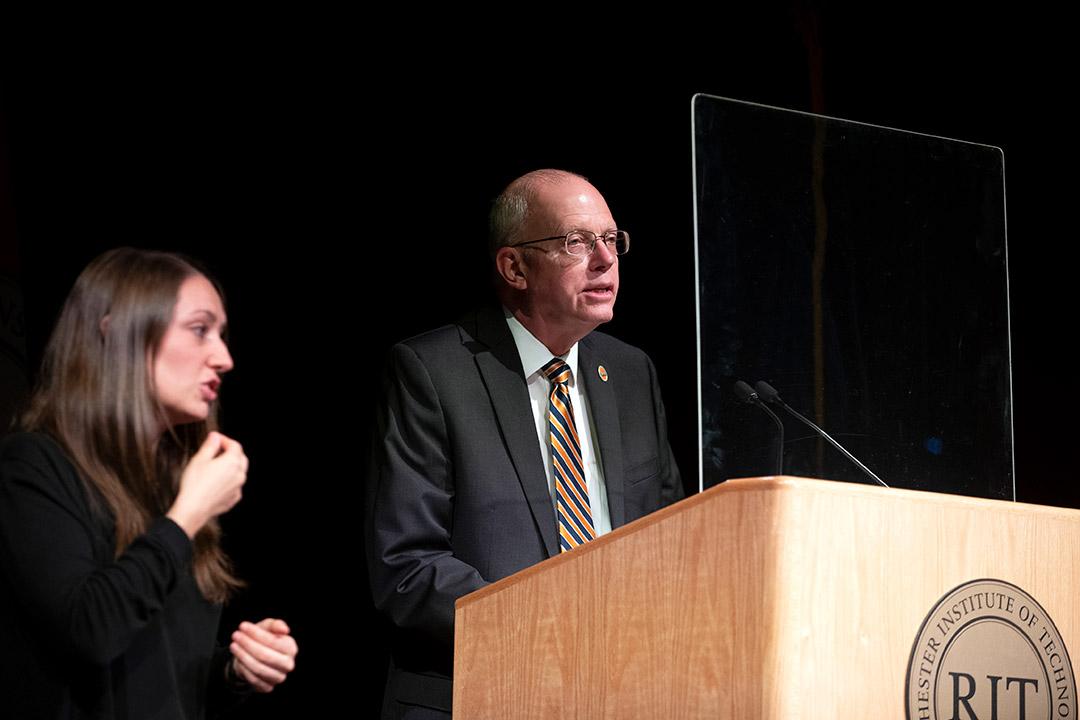 RIT President David Munson speaking at a podium next to an American Sign Language interpreter.