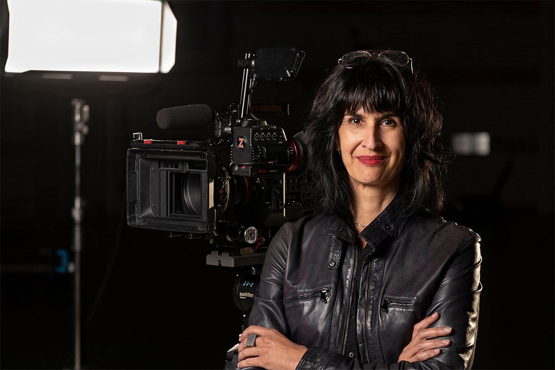 filmmaker Shanti Thakur posing with a camera.