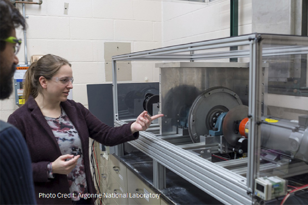 Woman in laboratory points at turbine machine for wind energy generation.