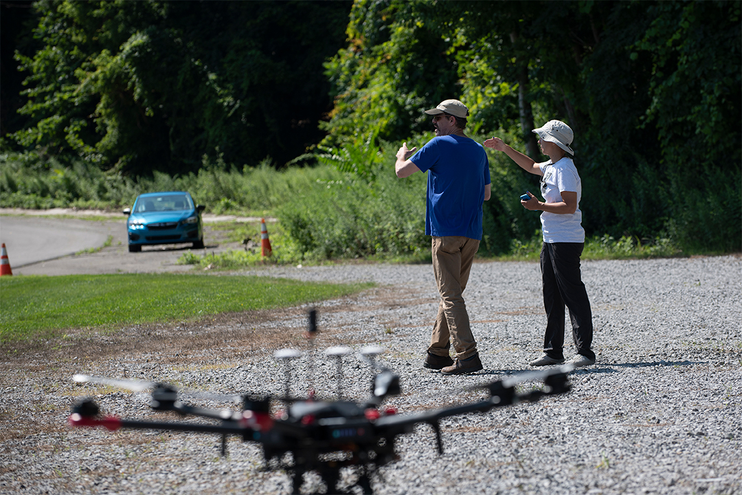 Two people walk next to a drone.