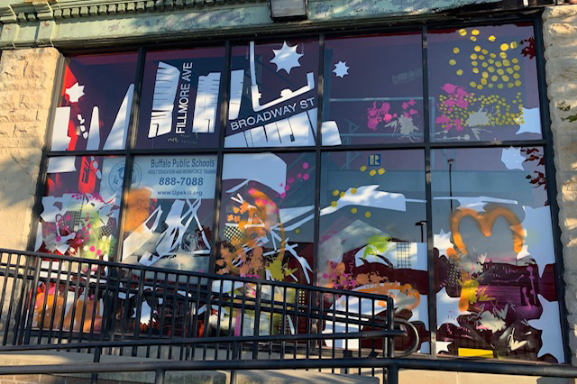 A storefront window display of abstract painting and printmaking.