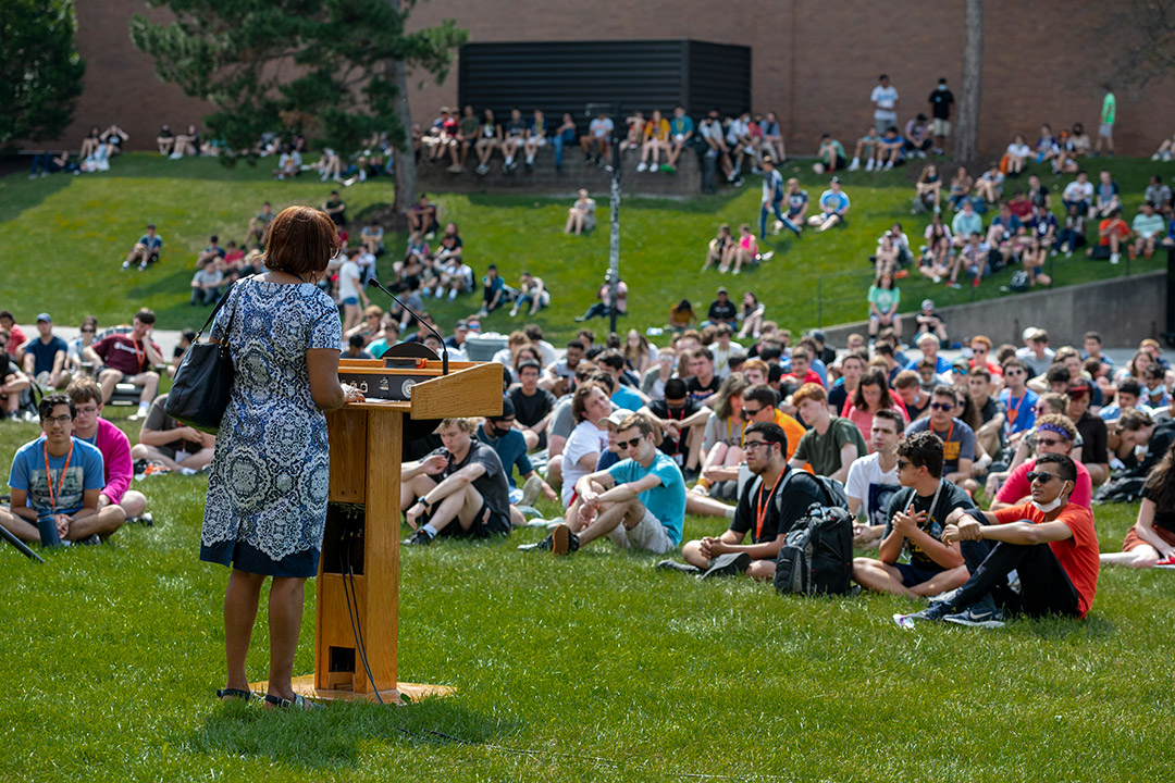 groups of students sitting on the grass listening to a speaker at a podium.