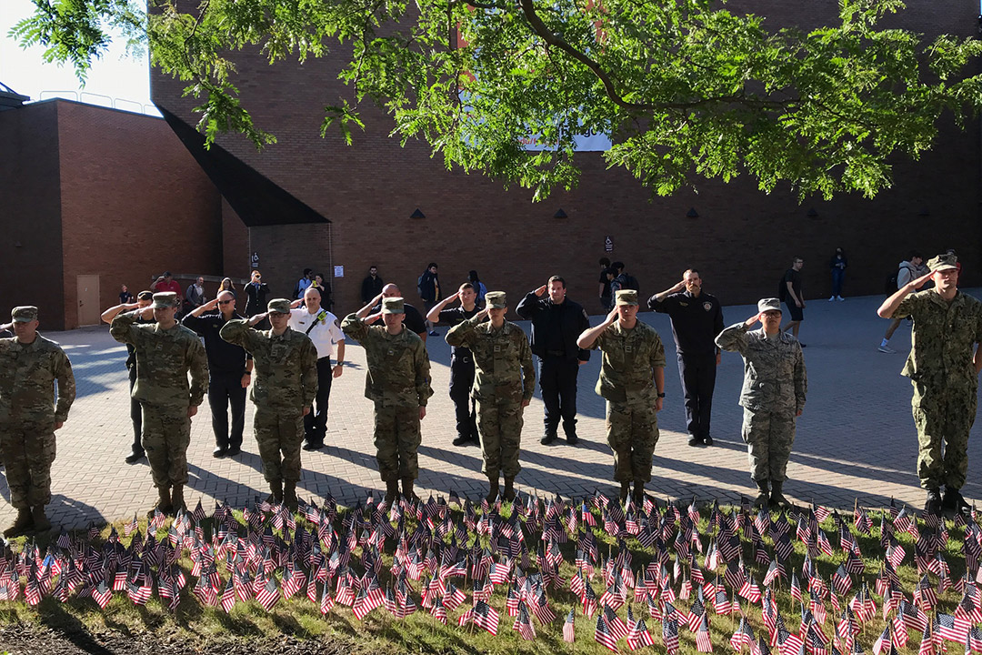 Army and Air Force ROTC students saluting a field of American flags.