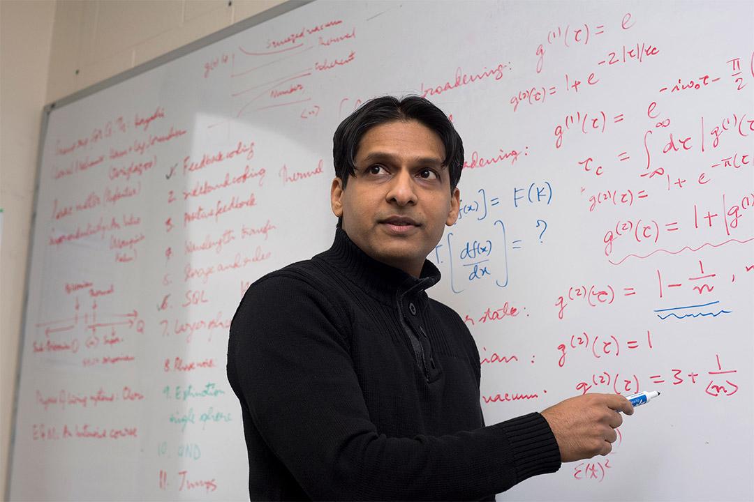 professor writing math equations on a dry-erase board.