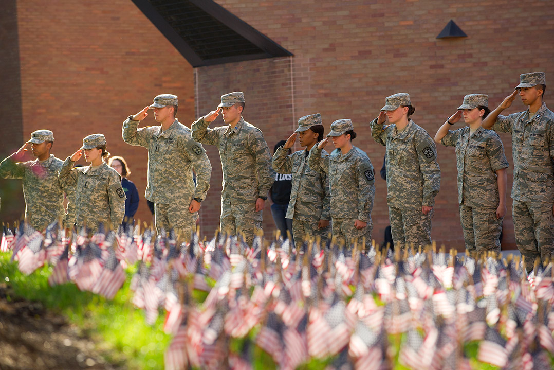 ROTC members saluting in front of a field of small American flags.
