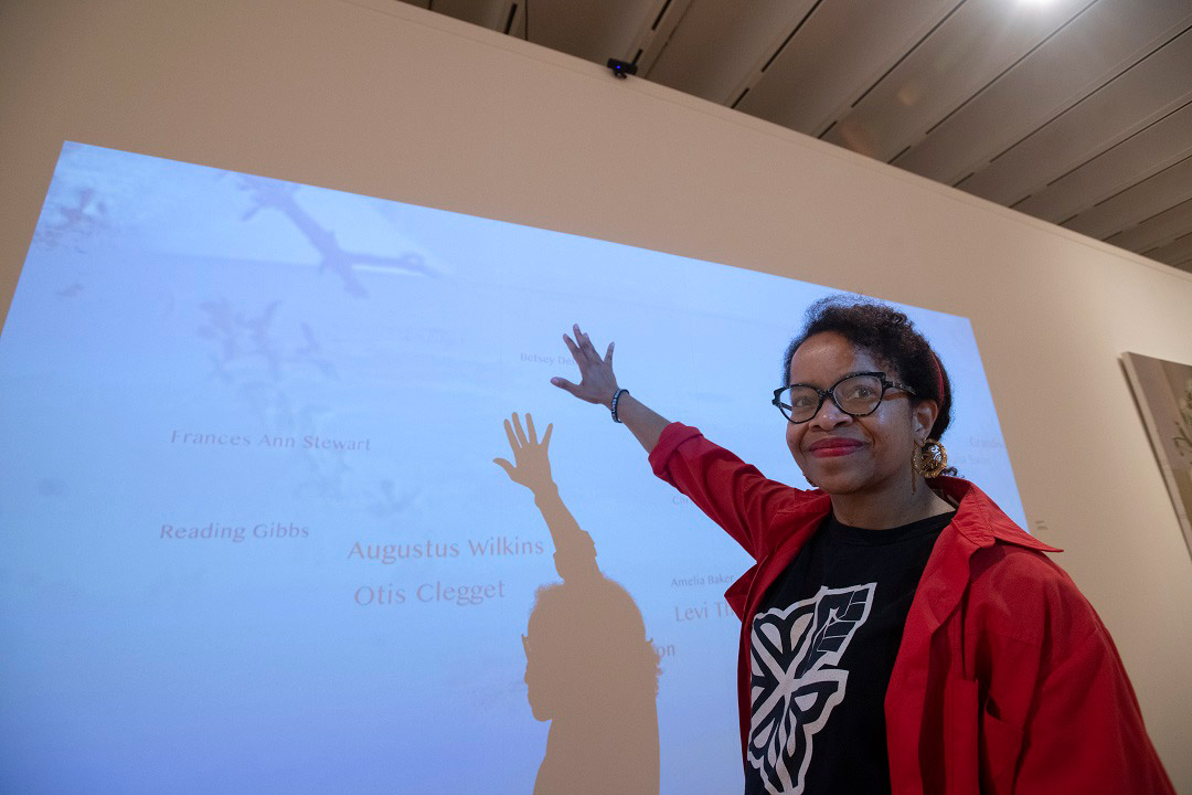 professor standing in front of an interactive digital memorial.