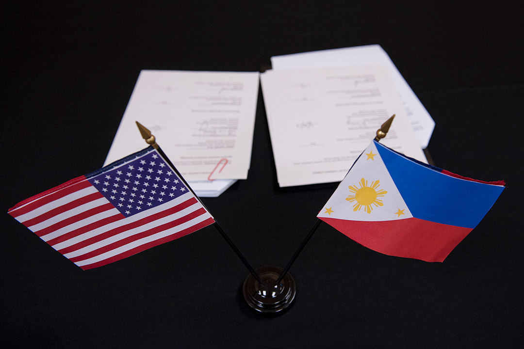 small American and Phillippine flags in the foreground and paperwork in the background.