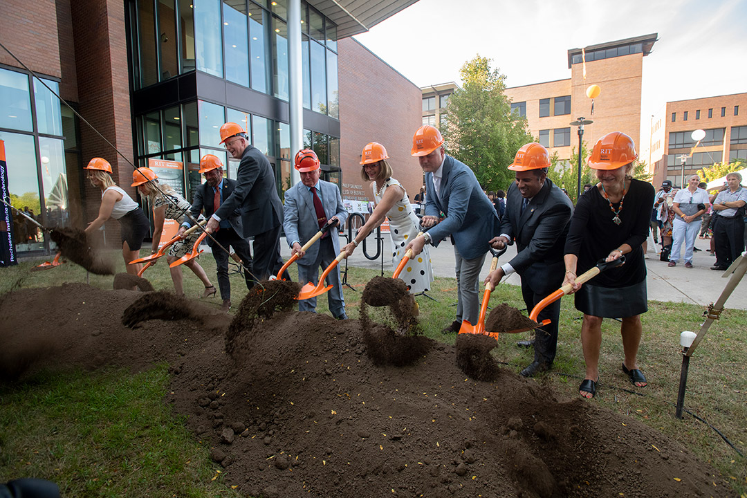 nine people wearing hard hats using shovels to dig a small portion of dirt in a ceremonial groundbreaking.