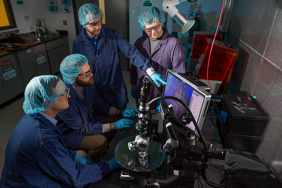 group of four scientists looking at a microchip.