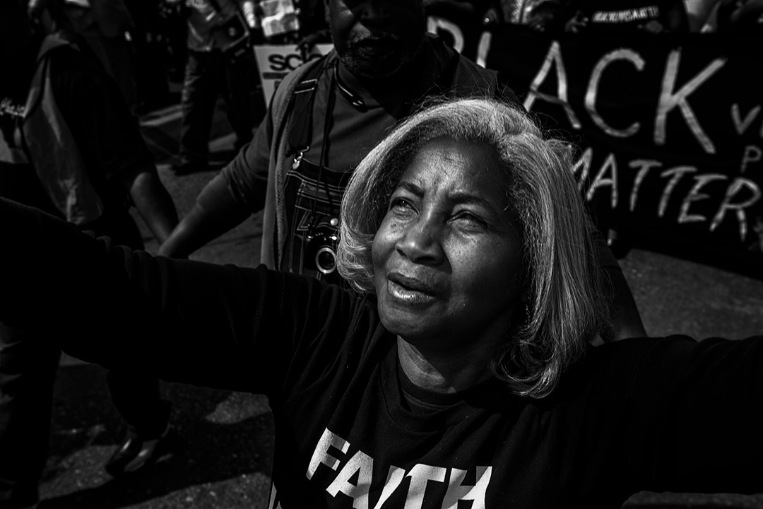 'black and white photo of a woman with her arms outstretched and a Black Lives Matter sign in the background.'