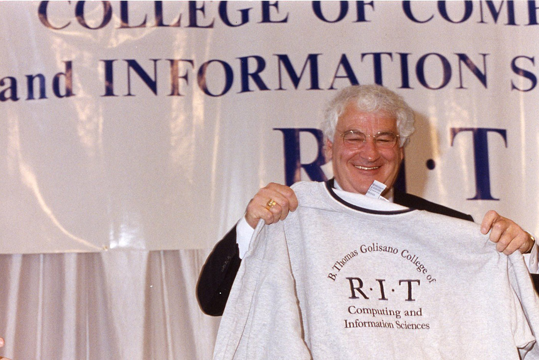 man holding sweatshirt with the words B. Thomas Golisano College of Computing and Information Sciences.